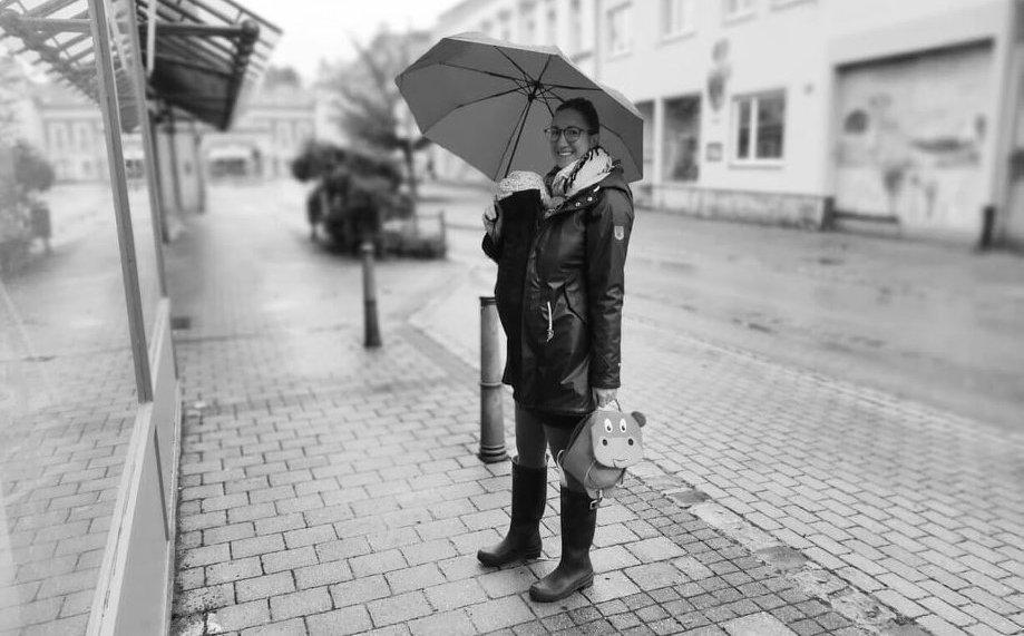 Mami trägt ihr Kind in der Trage und hält einen Regenschirm